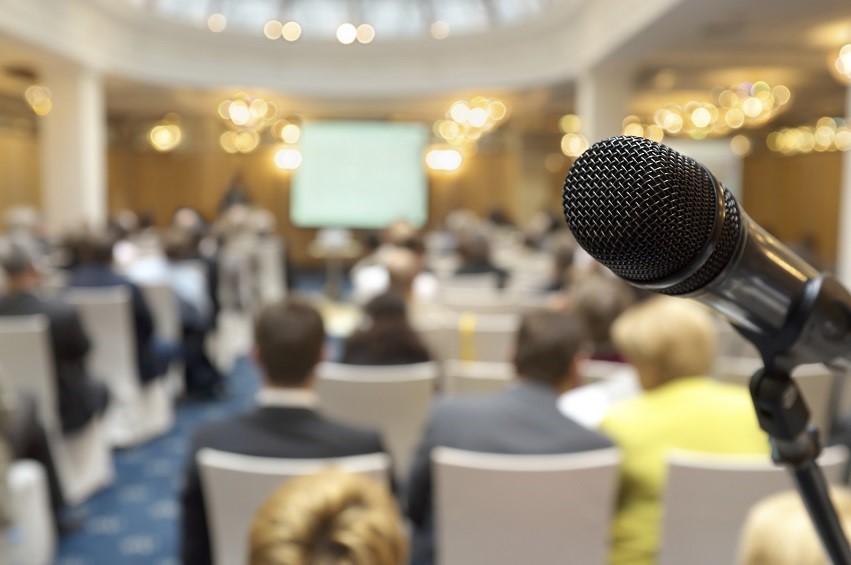 Microphone at conference hall. Dynamic microphone against the background of convention center. Real photo.